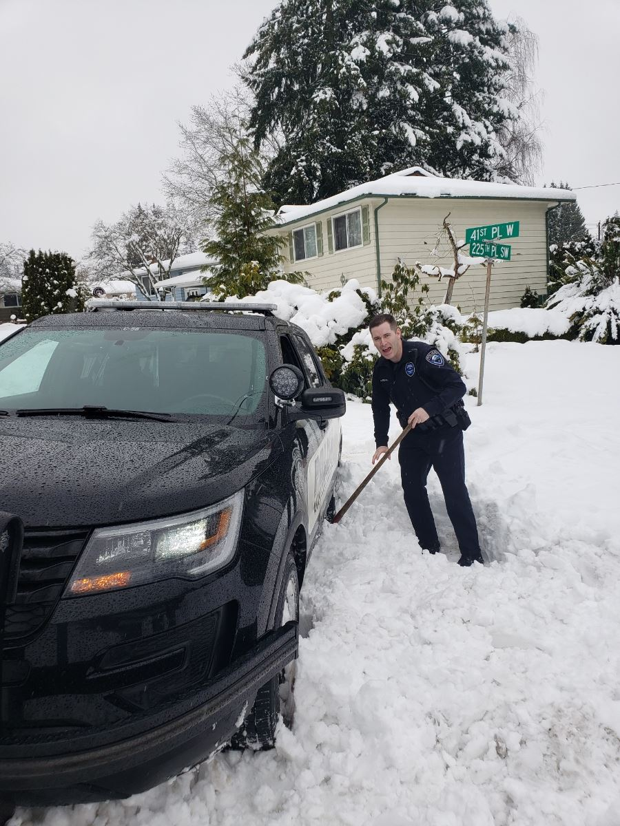 Police Officer digging out a car in snow